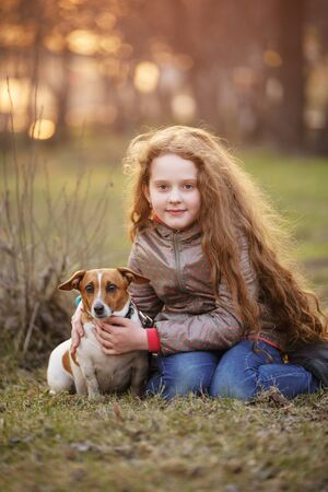 Little girl hugging her friend a dog in the outdoors. Friendship, animal protection, lifestyle concept. Banco de Imagens