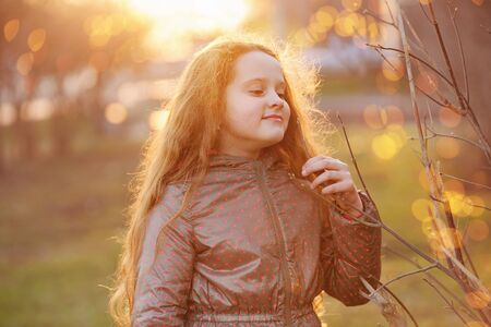 Little girl holding young green tree branch in sunlight. Healthy, lifestyle, earth hour, ecology concept. Stockfoto - 128618804