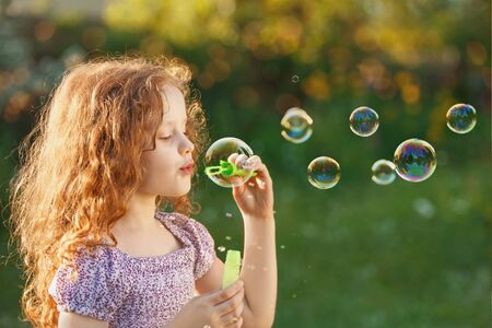 Little girl blowing soap bubbles in spring outdoors. Healthy, lifestyle, happy childhood concept.