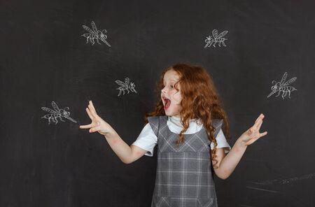 Triste petite fille qui a peur des piqûres de moustiques volant autour d'elle.