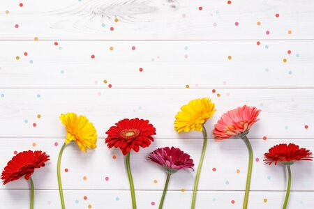 Red, yellow gerbera flowers with confetti on wooden background. Holiday, Easter, Birthday concept. Foto de archivo - 128853875