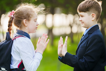 School child friend enjoying clapping hands, or playing patty cake, or giving high five having fun together in spring park.
