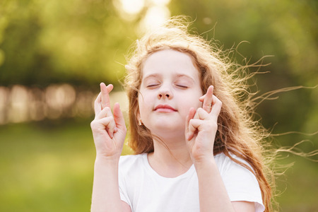 Little redhead girl  raises fingers crossed and makes desirable wish outdoors.
