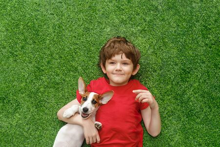 Child embracing puppy jack russell and lying on green carpet. High top view. Foto de archivo - 128854016