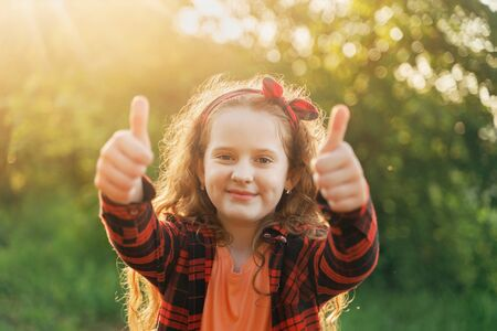 Cute girl with red bow in her hairs, showing thumbs up. Success, teamwork concept. Foto de archivo - 128854028