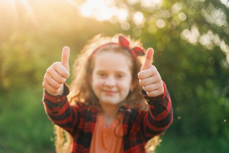 Cute girl with red bow in her hairs, showing thumbs up. Focus on hand. Foto de archivo - 128854031