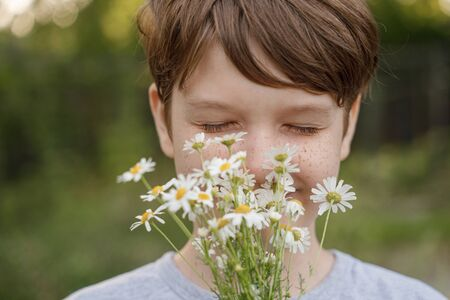 Smiling child with a bouquet of white daisy. Mothers day concept. Foto de archivo - 128854262