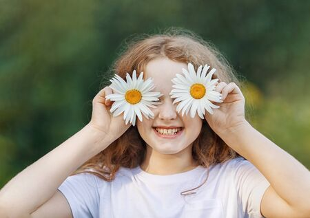 Child with daisy eyes showing white healthy  teeth  on green background in a summer park. Foto de archivo - 128854266