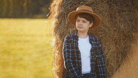 Teenage boy in straw hat standing near hay bale in a field, harvest concept. Foto de archivo - 128854263
