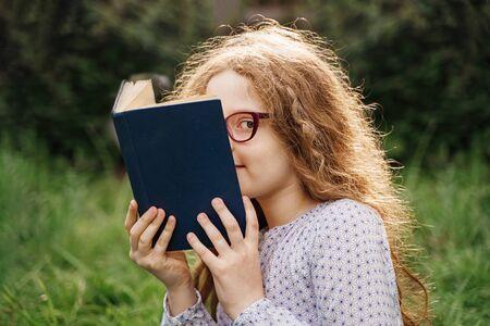 Kleines Mädchen, das draußen träumt oder ein Buch liest.
