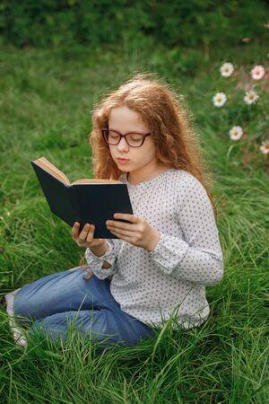 Kleines Mädchen, das draußen träumt oder ein Buch liest. Bildungskonzept.