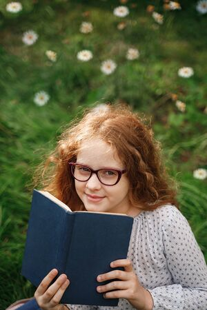 Little girl dreaming or reading a book in outdoors. Education concept. Foto de archivo - 128854272