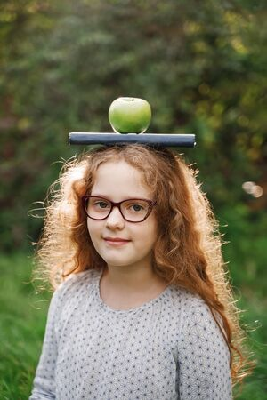 Laughing girl with a book and apple on his head. Easy learning concept. Foto de archivo - 128854269