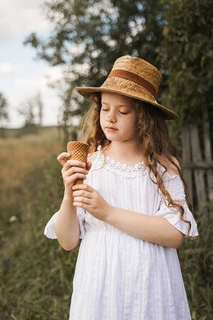 Curly girl in a straw hat eats ice cream in the village in the summer.Retro vintage, happy childhood concept. Foto de archivo - 128854306