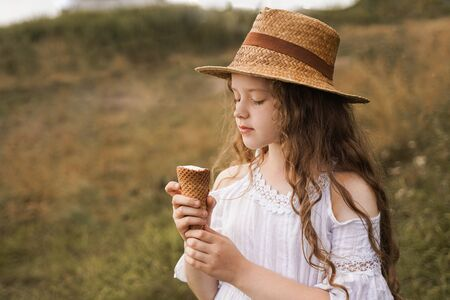 Curly girl in a straw hat eats ice cream in the village in the summer. Retro vintage, happy childhood concept.