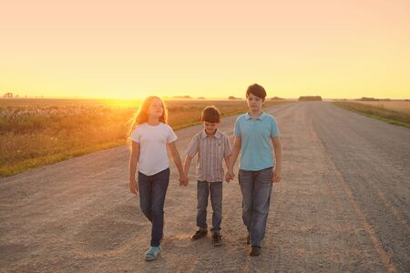 Children go on the road to meet the sunset. Freedom, movement, loneliness, humility concept. Foto de archivo - 128854320
