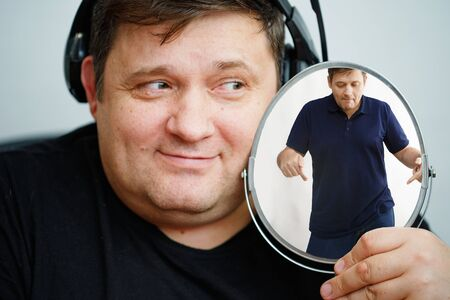 Man with a fat face holds a mirror and dreams of becoming slim. Diet, proper nutrition concept. Focus on the hand with a mirror.