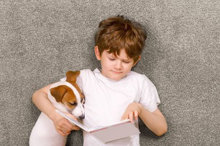 Child embracing friendly dog jack russell was reading the book and lying in green carpet. Education, happy childhood concept. Standard-Bild