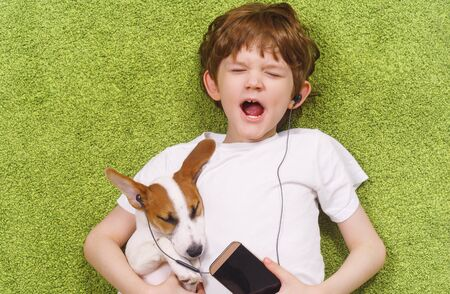 Little boy with a dog listen to music on the phone while lying on the carpet. Friendship, stay home concept.