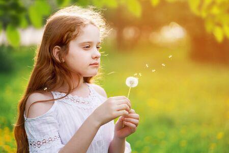 Beautiful child enjoy blowing dandelion in spring park.