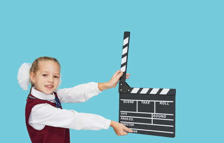 School girl with empty black filmmaking clapperboard on blue color background. Stock Photo