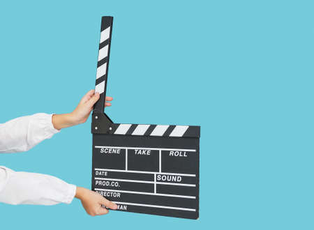 Child hands with empty black filmmaking clapperboard on blue color background.