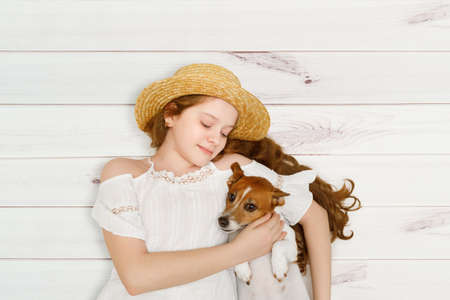 Little girl embracing her dog lying on a wooden floor.