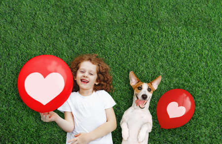 Laughing girl and puppy holding red balloon with heart. Mother's, Dad's, Valentine's Day concept. Happy spring day. Happiness concept.