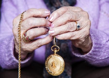manos: Dos manos ancianas sosteniendo entre los dedos un reloj dorado de bolsillo  Stock Photo