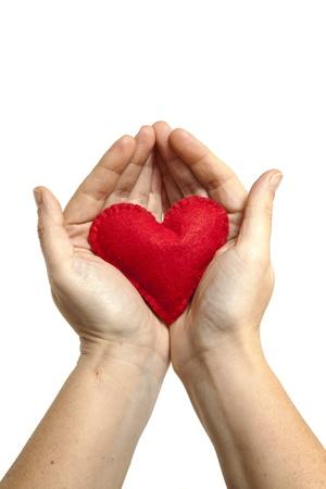 generosity: Dos manos que ofrecen un corazón rojo de fieltro hecho a mano sobre un fondo blanco