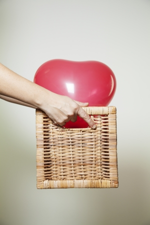 Delivering a red hearted baloon in a wicker box  photo