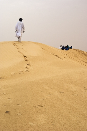 Tuareg men walking trough Sahara photo