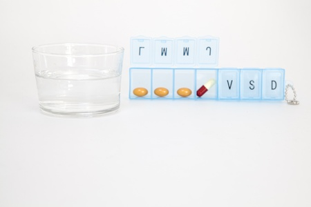 pillbox: Pillbox with daily medication and a glass of water