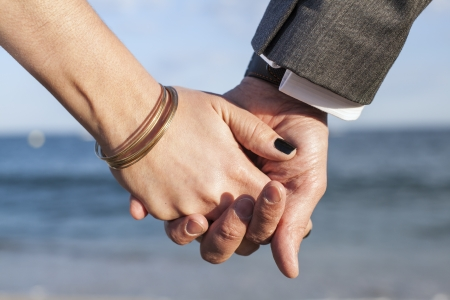 A couple grabbing each others hands with the mediterranean blue sea as background  The focus is on a hands  photo
