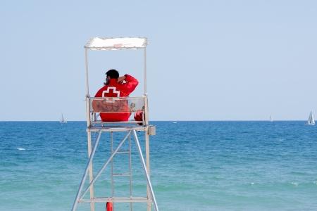 cruz roja: Lyfeguard sentado en la torre de vigilancia, mirando el mar Editorial