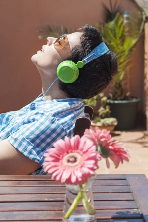 Young woman listening music at an urban terrace photo