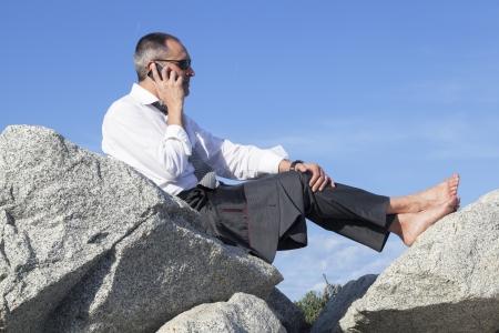 competitividad: La mediana edad hombre de negocios descansando sobre unas rocas en la playa mientras cheking correo electr�nico en su tel�fono inteligente