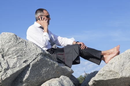 competitiveness: Middle age business man resting over some rocks at the beachside while cheking emails at his smartphone