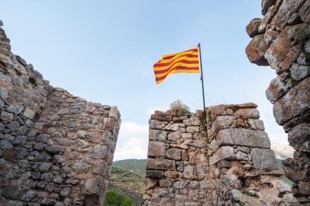 Catalan flag waving over a ruined castle Reklamní fotografie