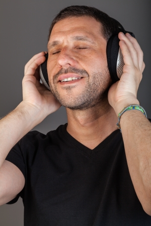 25 to 30: Smiling man listening to music