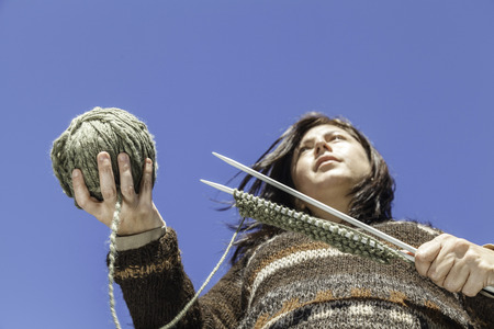 The young woman holding a knitting equipment 免版税图像