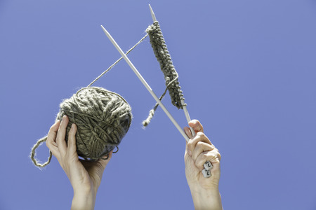 A knitting equipment hold with two hands with the blue sky