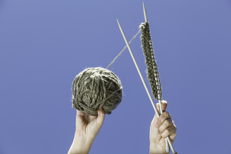 disconnection: A knitting equipment hold with two hands with the blue sky Stock Photo