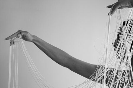 black and white Image of the profile of a young attractive woman with uncovered shoulders, who decoratively draws the white threads of a string curtain with her hands, isolated, copy space 写真素材