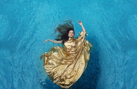 beautiful young woman in gold dress, evening dress floating weightlessly elegant floating in the water in the pool