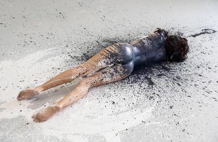 Jeune femme en sous-vêtements, vêtements de sport, artistiquement abstraite peinte avec une grande éclaboussure de peinture noire, se trouve sur le sol dans le studio, copiez l'espace.