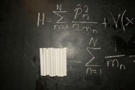 Close up image of a pile/bunch of white chalks on a blackboard with a written mathematical formula