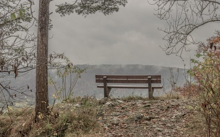 bench with view into a valley on a rainy day