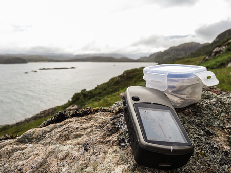 Geocaching in Scotland with GPS device and cache container Stock Photo