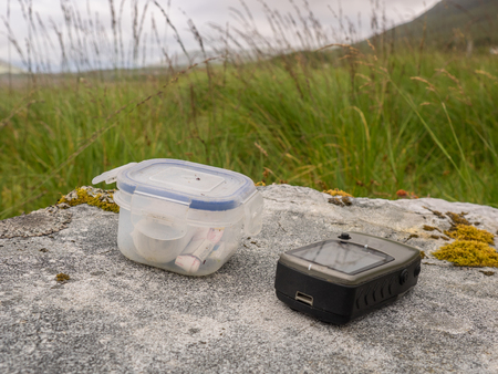 Geocache with GPS device on a big rock with grass background Imagens